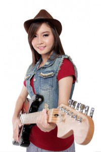 Pretty Asian guitarist girl in jeans jacket and fedora hat smiles at camera while holding her electric guitar, on white background