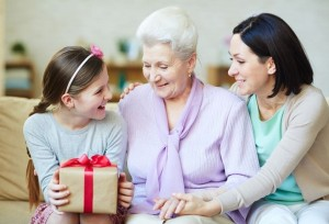 Young and elderly women looking at gift-box held by teenage girl