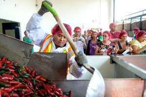 Employee Victor Avila pushes the chili down the hopper machine during chili grinding process at Huy Fong Foods in Irwindale, Calif., on Friday, Aug. 22, 2014. (AP Photo/San Gabriel Valley Tribune, Watchara Phomicinda) MAGS OUT; NO SALES; MANDATORY CREDIT